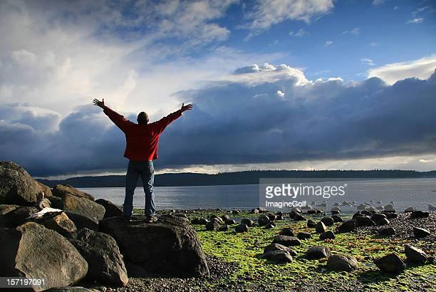 Homme soulevant ses mains vers le paradis dans un superbe cadre avec vue sur l'océan
