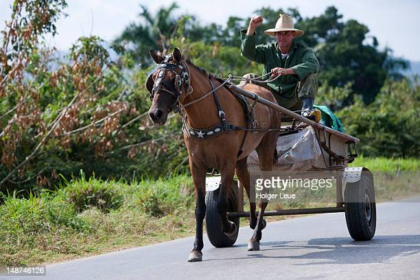 Man raising revolutionary fist while riding on horse carriage.