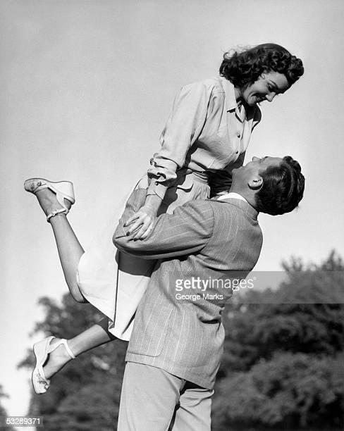 man raising woman in the air - amour noir et blanc photos et images de collection