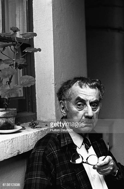 Man Ray, an American photographer, filmmaker, and painter sits outside a house. Man Ray was a major figure in the development of Modernism and...