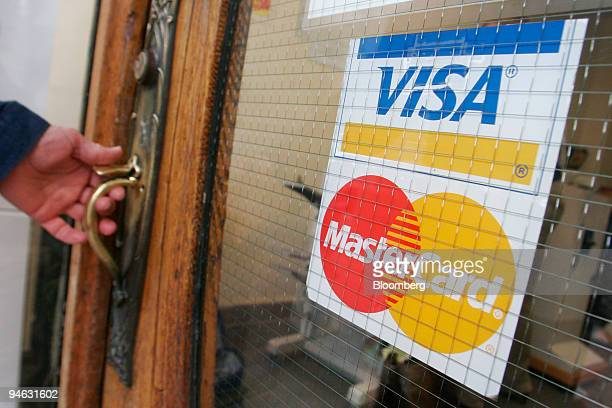 A man reaches for a door advertising acceptance of VISA and MasterCard at Gnomon Copy in Cambridge Massachusetts on Wednesday October 11 2006 Visa...