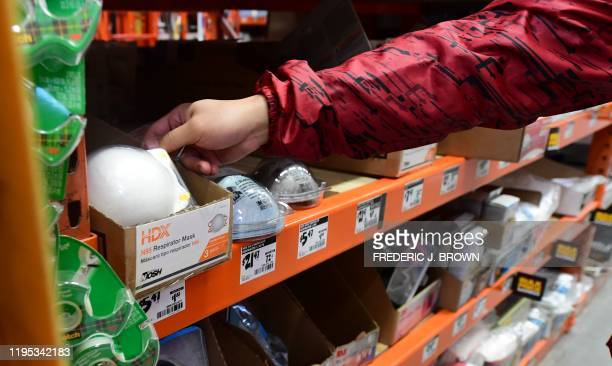 A man reaches out for a mask at a Home Depot store in Los Angeles California on January 22 2020 as the Coronavirus entered the United States this...