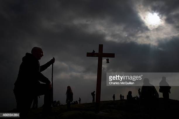 Man reaches out to touch the cross situated where St. Patrick used to sit on a rock tending sheep as hundreds of people make the St. Patrick's Day...