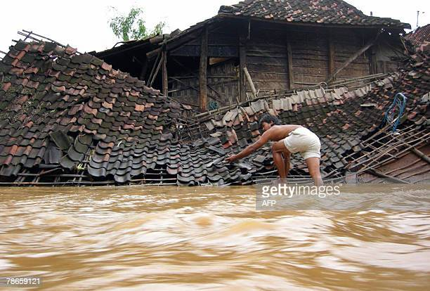 A man reaches the roof of his destroyed house in Ponorogo of East Java province 27 December 2007 Hundreds of Indonesian rescuers resumed a grim hunt...