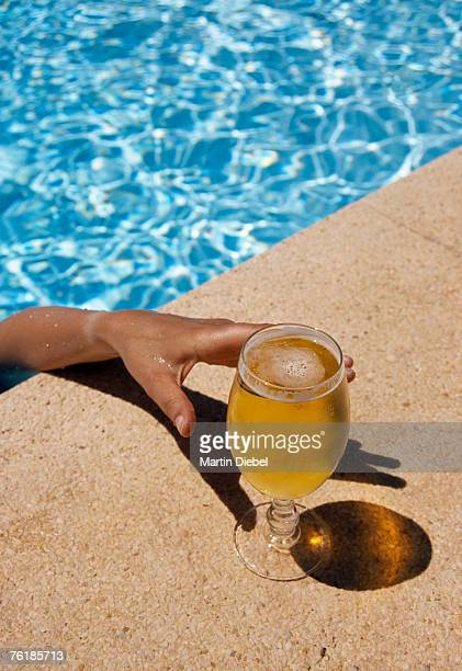 A man reaching for a glass of beer from a swimming pool