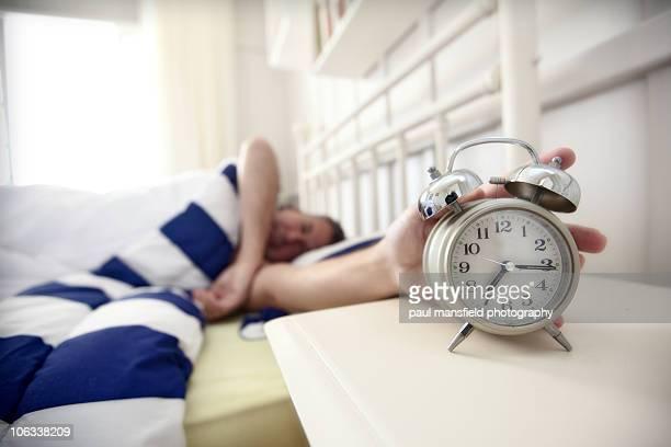 Man reaching for alarm clock