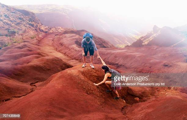Man reaching for arm of woman hiking in canyon
