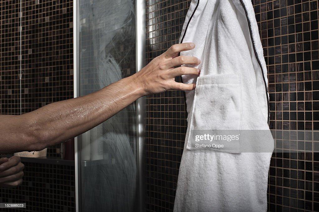 Man reaching for bathrobe in shower : Foto de stock