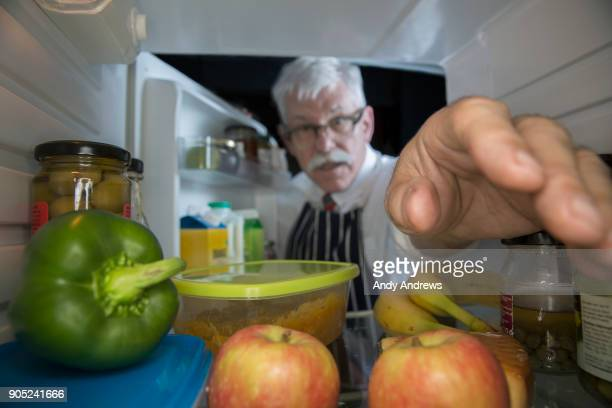 POV Man reaching for food in a refrigerator