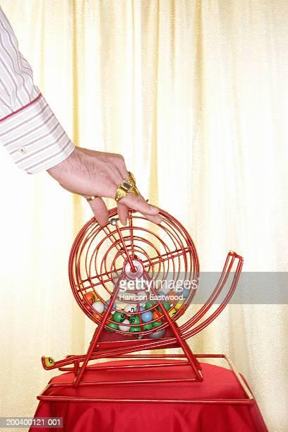 Man reaching for handle on manual bingo machine, close-up of hand