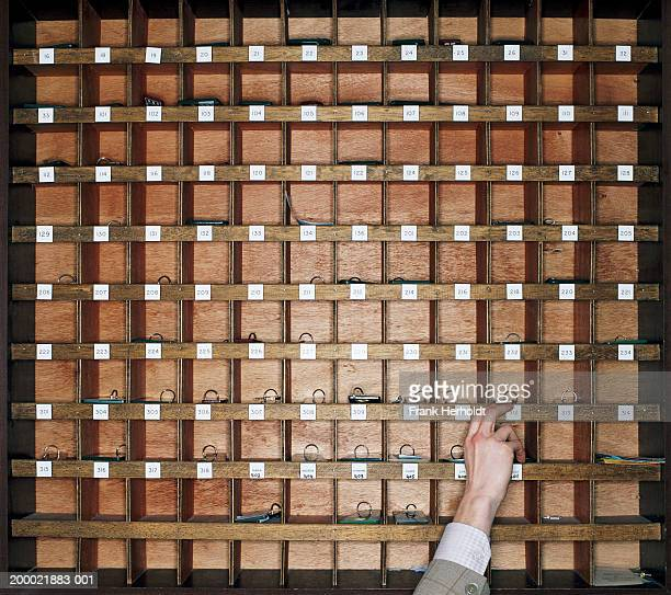 Man reaching for key in pigeonhole