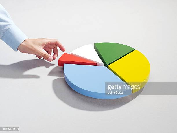 man reaching for segment of pie chart - pie chart stock pictures, royalty-free photos & images