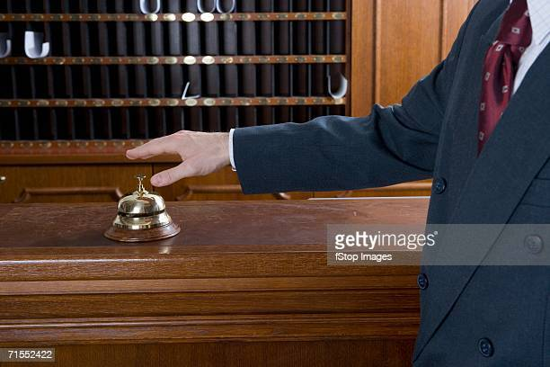 Man reaching for service bell on desk at hotel reception