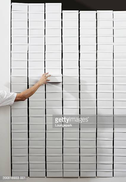 Man reaching for shoebox in stack