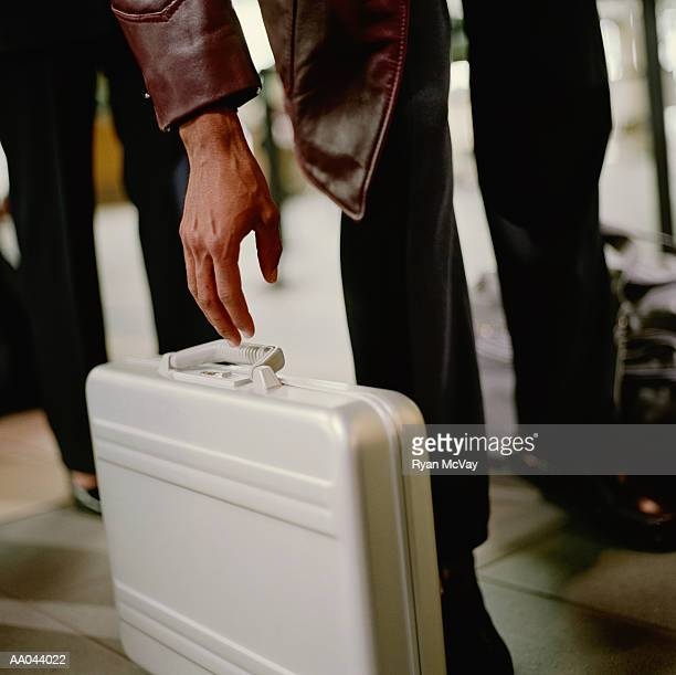 Man reaching to pick up briefcase, low section
