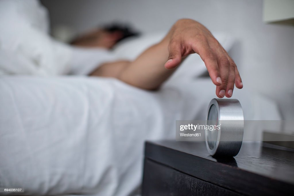 Man reaching to turn off alarm clock : Stock Photo