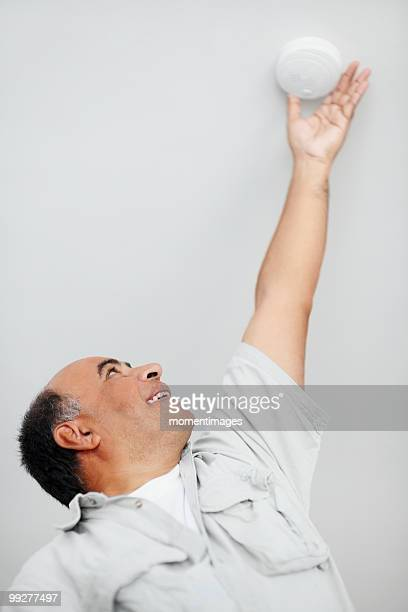 Man reaching up to smoke detector