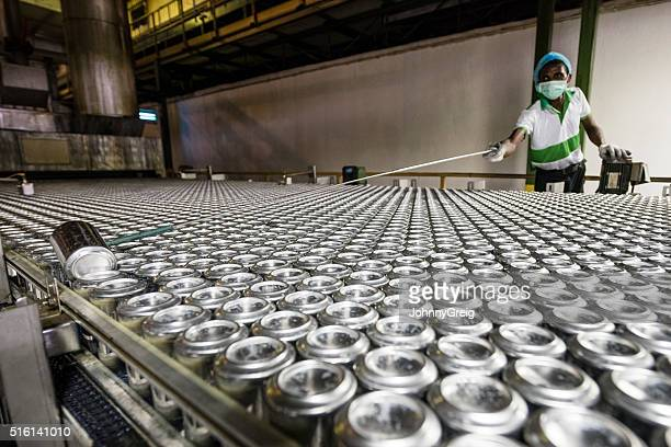 Man reaching with tool in aluminium can processing plant