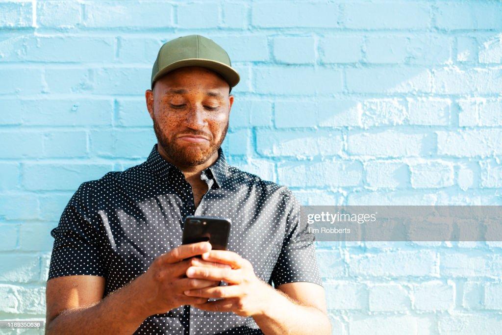 Man reacting to smart phone : Stock Photo