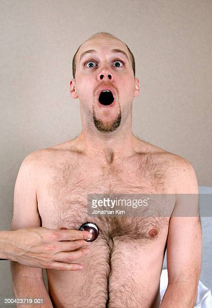 man reacting to stethoscope being placed on chest, close-up - hairy man chest stock photos and pictures