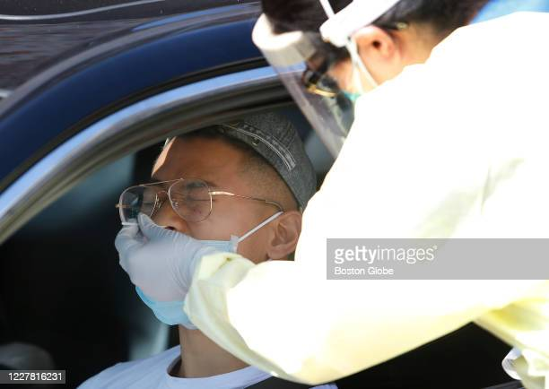 Man reacts as a dental hygienist administers a COVID-19 test at the NEW Health COVID-19 testing site in Charlestown in Boston, MA on July 27, 2020.