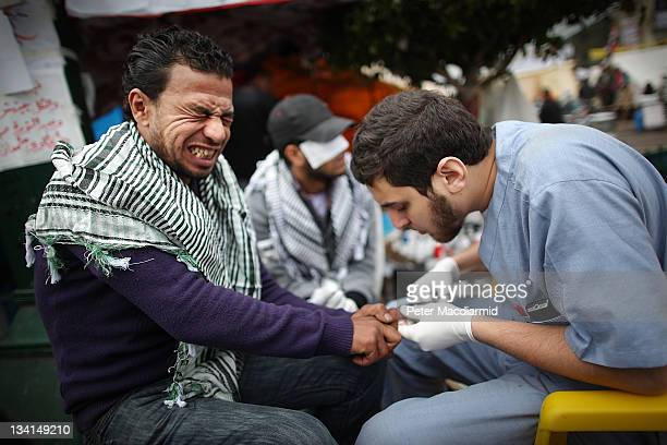 A man reacts as a medic stitches a wound at a make shift first aid post in Tahrir Square on November 27 2011 in Cairo Egypt Protestors are continuing...