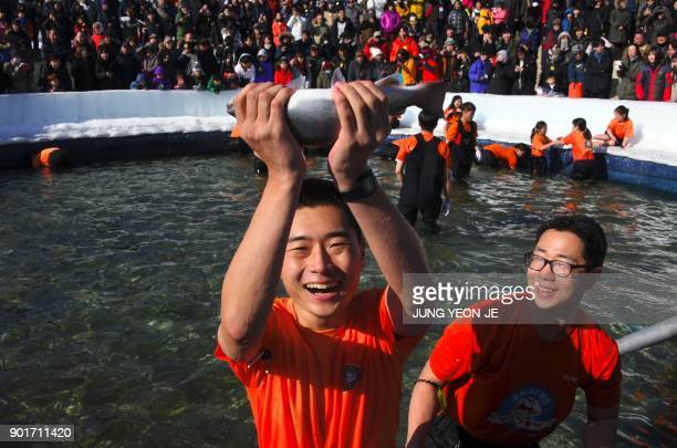 A man reacts as he catches a trout by barehand fishing during the annual ice fishing festival in Hwacheon some 120 kilometers northeast of Seoul on...