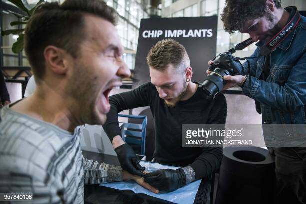 A man reacts as he gets a chip implant in his hand during a chip implant event in Epicenter a technological hub in Stockholm on January 18 2018 An...