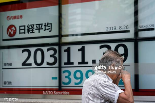 Man reacts as he looks at an electronic stock board displaying the Nikkei 225 Stock Average figure on August 26, 2019 in Tokyo, Japan. Japanese...