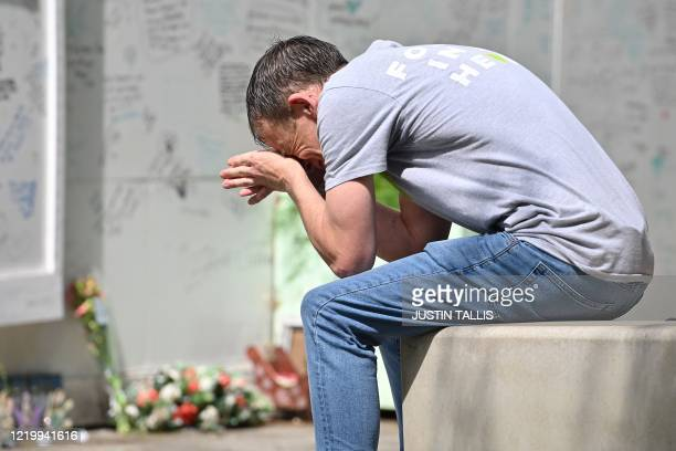 A man reacts as he pays his respects in front of Grenfell tower in west London on June 14 on the third anniversary of the highrise fire that killed...