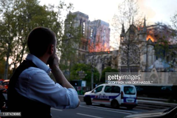 A man reacts as he watches the flames engulf the roof of the NotreDame Cathedral in Paris on April 15 2019 A huge fire swept through the roof of the...