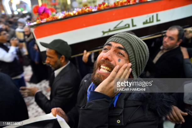 Man reacts as Iraqi mourners carry a coffin draped in the national flag during a funeral in the central holy shrine city of Najaf on December 13 for...