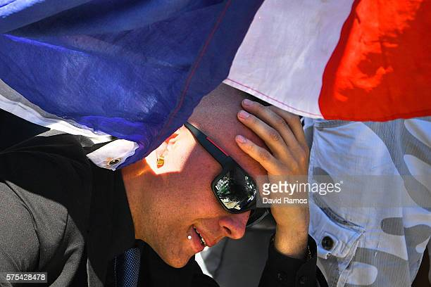 A man reacts as people visit the scene and lay tributes to the victims of a terror attack on the Promenade des Anglais on July 15 2016 in Nice France...