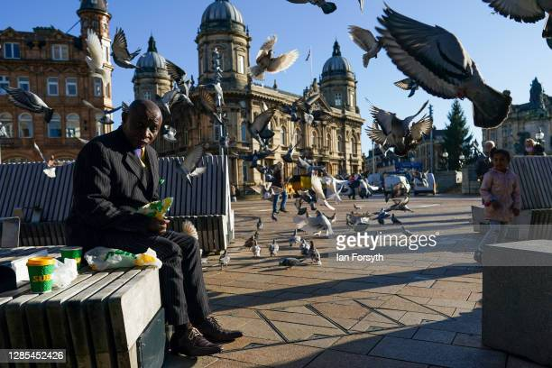 Man reacts as pigeons take flight around him in Hull city centre on November 13, 2020 in Hull, England. Hull recorded 726.8 new cases per 100,000...