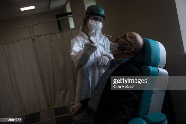 Man reacts before having a COVID-19 nose swab test done at the Kartal Dr. Lutii Kirdar Education and Research Hospital on May 08, 2020 in Istanbul,...