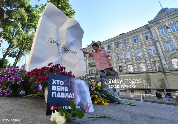 Man reacts by a memorial to journalist Pavel Sheremet on the site where Sheremet's car exploded on the 4th anniversary of his death in Kiev on July...