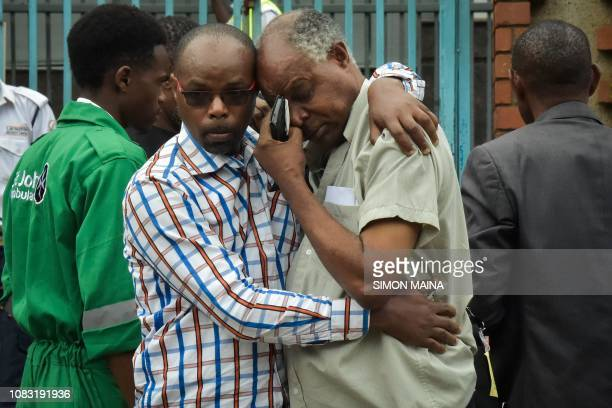 A man reacts in the arms of a relative in Nairobi on January 16 while identifying the bodies of the victims after a blast followed by a gun battle...