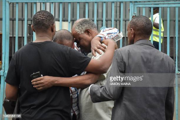 A man reacts in the arms of relatives in Nairobi on January 16 while identifying the bodies of the victims after a blast followed by a gun battle...