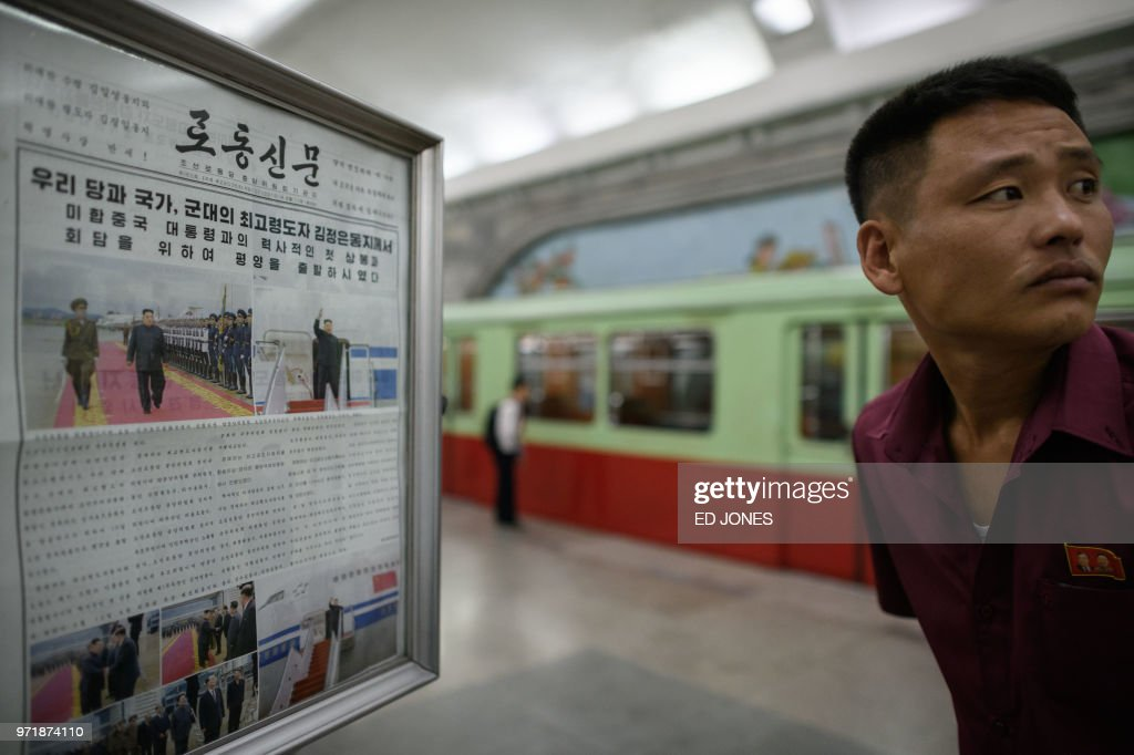 TOPSHOT - A man reacts next to a displayed Rodong Sinmun newspaper showing images of North Korean leader Kim Jong Un in Singapore ahead of his meeting with US president Donald Trump, at a news stand on a subway platform of the Pyongyang metro on June 12, 2018. - Donald Trump and Kim Jong Un became on June 12 the first sitting US and North Korean leaders to meet, shake hands and negotiate to end a decades-old nuclear stand-off.