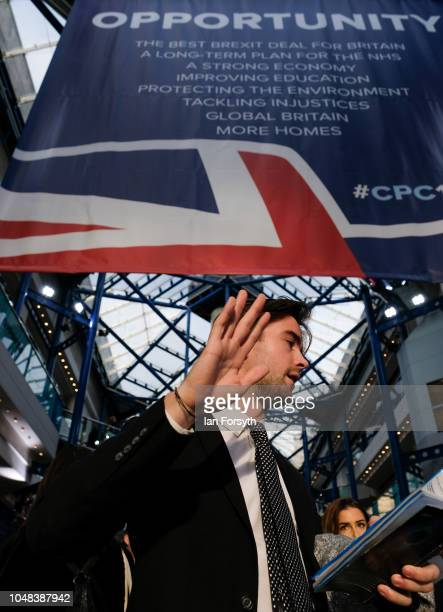 A man reacts to the camera as delegates gather inside the International Convention Centre at the close of day three at the Conservative Party...