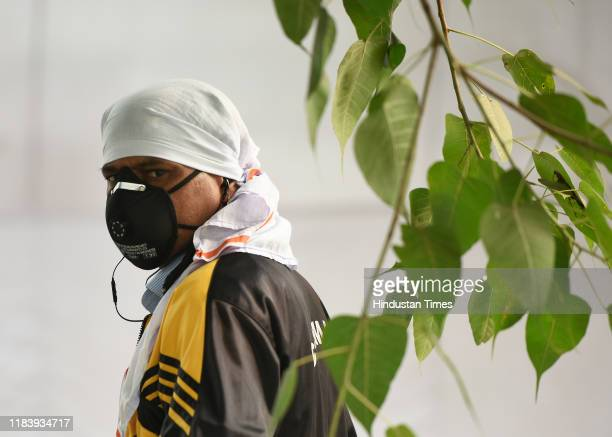 Man reacts to the camera while wearing an anti pollution mask amid smog at Sanjay Lake on November 22, 2019 in New Delhi, India. After being in...