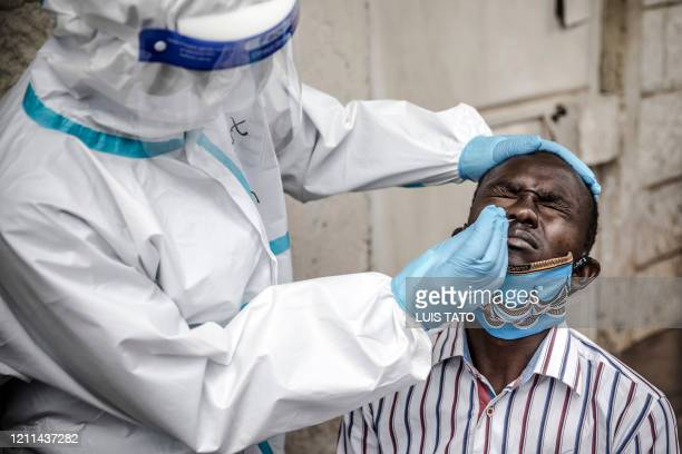 Man reacts while a health worker wearing personal protective equipment uses a nasal swab to collect a sample during the COVID-19 coronavirus mass...