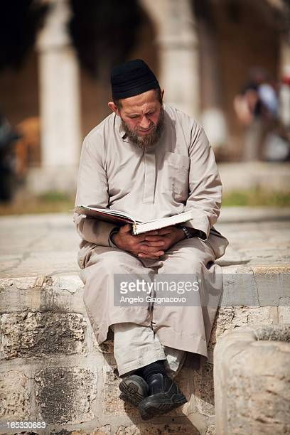 Man read a book sitting in a Dome of The Rock in Jerusalem, Israel.