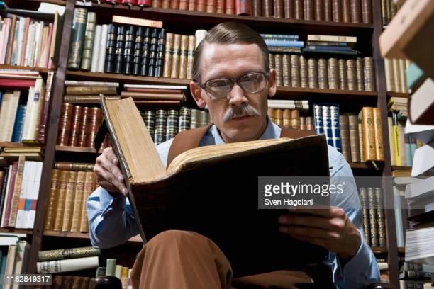 a man reading a book in a bookstore - literatur stock-fotos und bilder