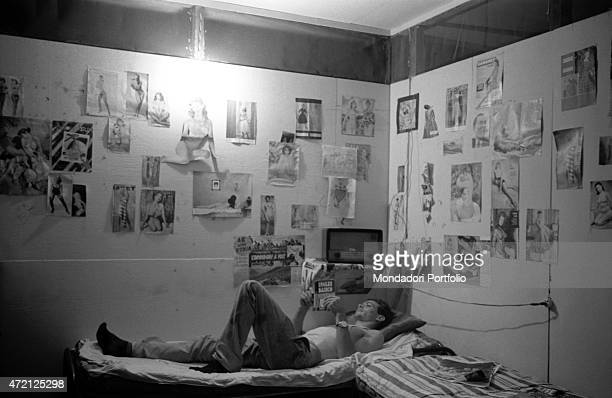 'A man reading a book in a room with walls covered in pictures of pin ups Caracas January 1958 '