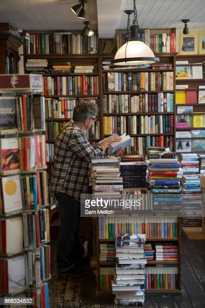 A man reading a book in John Sandoe bookshop on 19th October 2015 in London United Kingdom Independent bookshop since 1957 crammed with thousands of...