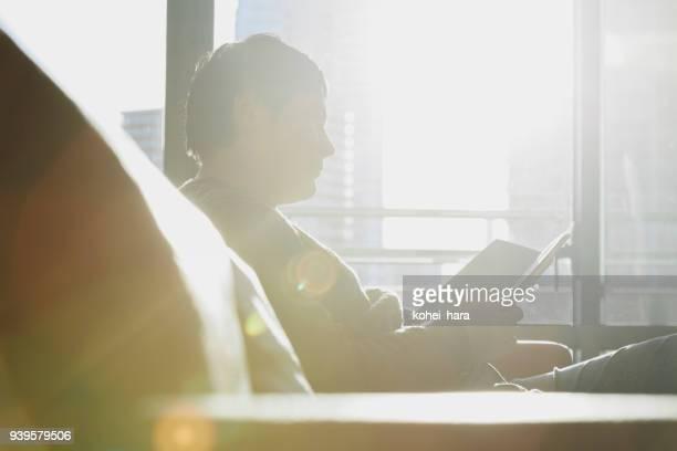 ソファーで本を読んでいる人 - シンプルな暮らし ストックフォトと画像