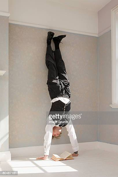 man reading a book upside down - handstand stock pictures, royalty-free photos & images