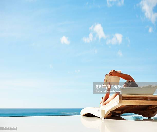 man reading a book while lying on deckchair - deck chair stock pictures, royalty-free photos & images