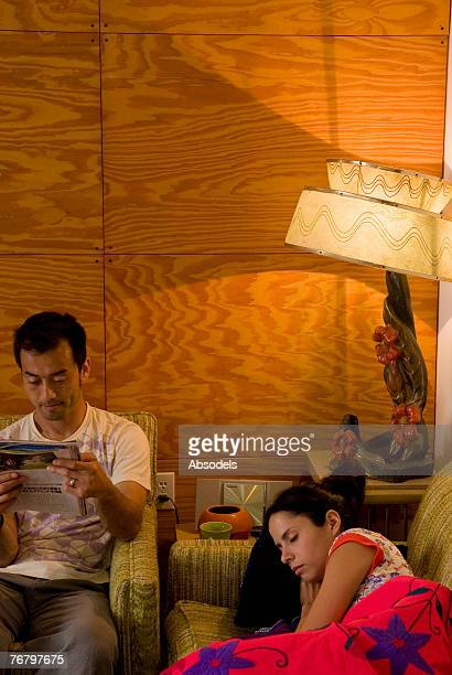 a man reading a bookend a woman sleeping - bookend stock pictures, royalty-free photos & images